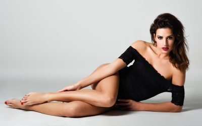 Young brunette woman in black lingerie lying on the floor. Attractive girl, model of fashion. Studio shot.